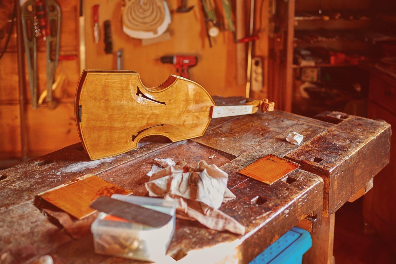 Nieukończone skrzypce na stole w zakładzie lutniczym