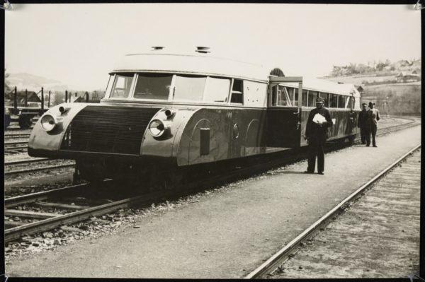 Fotografia czarno-biała. Wagon lukstorpedy stojący na stacji, przy nim dwóch konduktorów i pasażer.